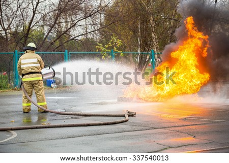 Fireman in uniform puts out the large flames with the help of a foam