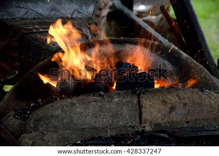 Fireplace of reconstructed medieval blacksmith with burning fire