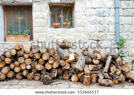 Firewood for the stove piled against the wall near the kitchen in the courtyard of an old house