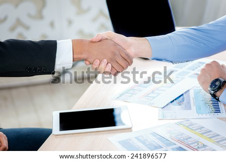Firm handshake. Two serious businessman sitting at the negotiating table in the office and shake hands. Business people dressed in formal wear