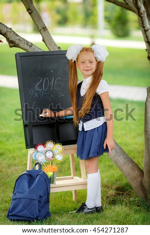 first grader writes at the blackboard