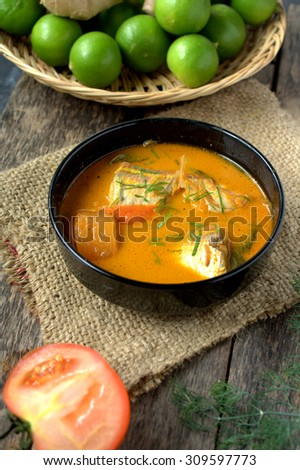 Fish curry with tomato and brinjal. Served in black bowl with wooden background.