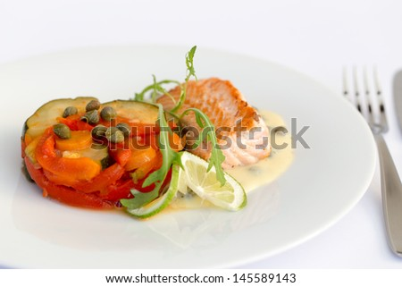 Fish fillet with lemon, vegetables and sauce in white plate.