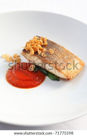 fish served elegantly with tomato sauce