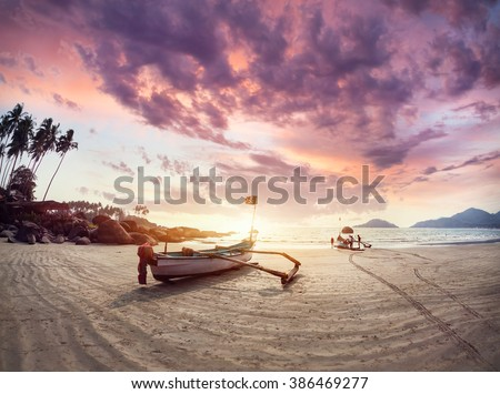 Fisherman boat on the tropical beach at sunset of Dreamy Palolem beach in Goa, India