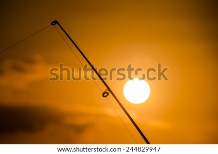 Fisherman Fishing Rod Silhouette at Orange Sunset
