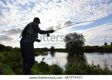 Fisherman in river, evening sunlight