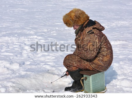 Fisherman on ice fishing on the reservoir in eastern Siberia