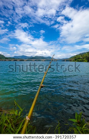 Fishing rod made of tree branch at a tropical lake and islands in cloudy blue sky. Belum resort, Banding, Temenggor Lake. Malaysia