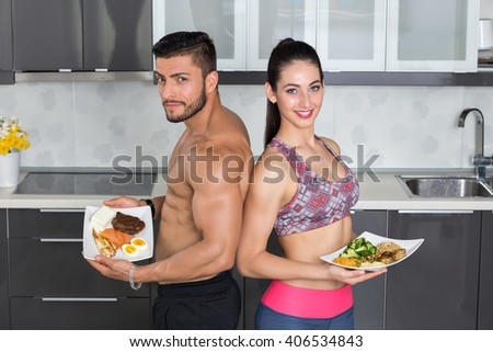 fit couple in the kitchen; animal versus plant proteins: one plate with beef, eggs, salmon, cheese and chicken grill and another with nuts, mushrooms, broccoli, lentil, hummus and quinoa