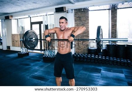 Fit man lifting barbell at gym