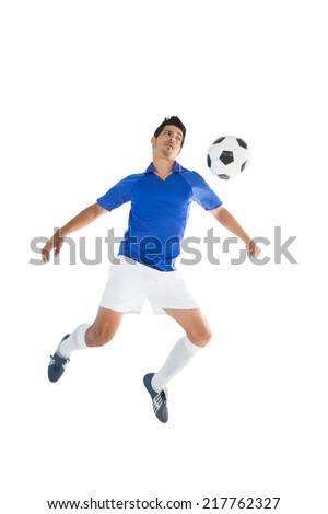Fit player kicking football over white background