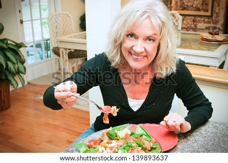 Fit, sexy senior woman eating a tossed green salad in her lovely modern home.