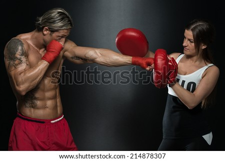 Fit Woman And Her Trainer Boxing Indoors - Bodybuilding Couple Posing With Boxing Gloves On Black Background