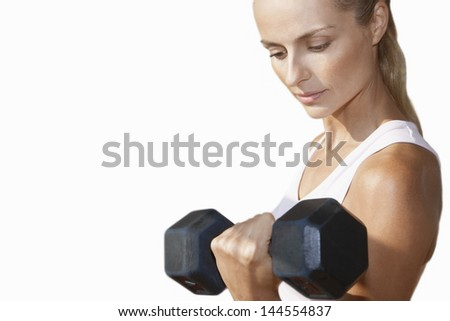 Fit young Caucasian woman lifting dumbbell isolated over white background
