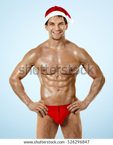 fitness bronzed handsome sexy Santa Claus , on blue background