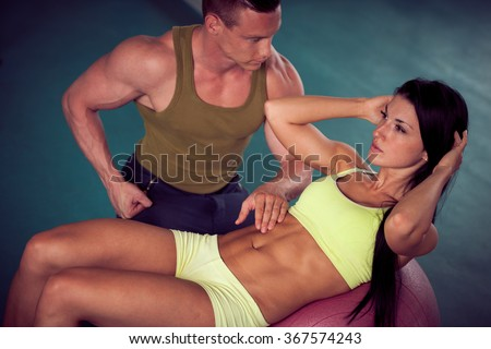Fitness couple workout - fit mann and woman train in gym