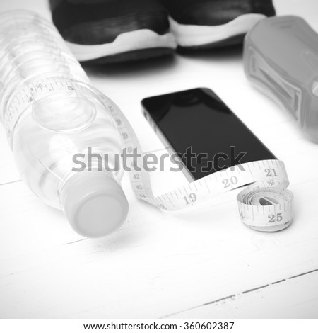 fitness equipment:running shoes,measuring tape,water,juice and phone on white wood background black and white color
