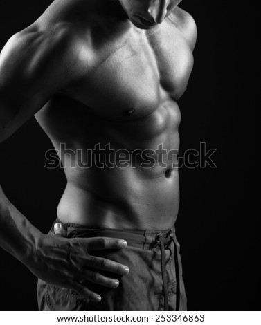 Fitness man posing on black background