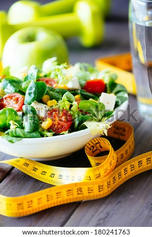 Fitness salad and measuring tape on rustic wooden table. Mixed greens, tomatos, diet cheese, olive oil and spices for healthy lifestyle concept.