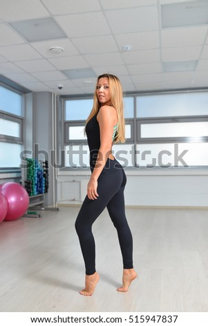 Fitness, sport, exercising lifestyle - woman in black bodysuit posing at gym
