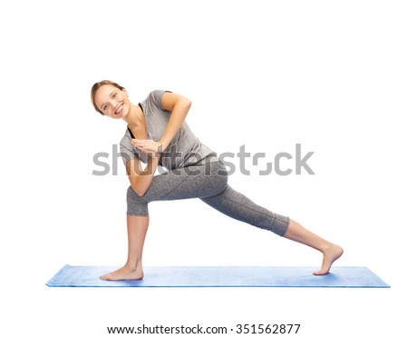 fitness, sport, people and healthy lifestyle concept - woman making yoga low angle lunge pose on mat