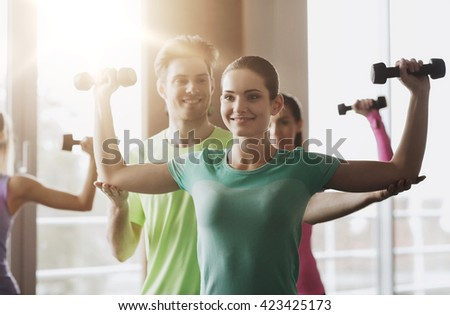 fitness, sport, training, gym and lifestyle concept - group of happy women and trainer with dumbbells flexing muscles in gym