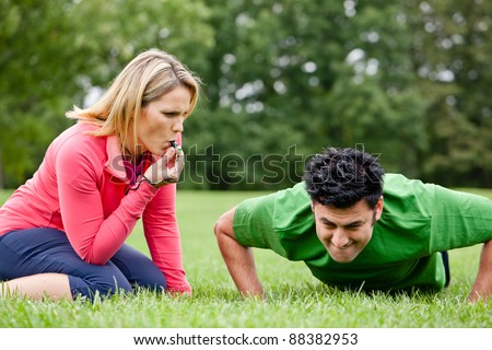 Fitness trainer coaching a trainee doing push ups