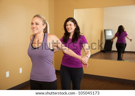Fitness Trainer Helping Young Woman Stretch Before Workout