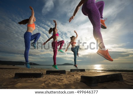 fitness, training, aerobics and people concept - group of girls working out with steppers on the beach (Focus on front female body)