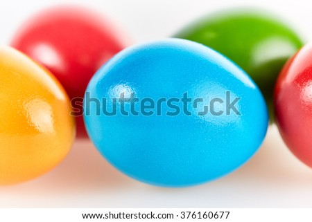 Five colorful easter eggs in different colors lying on white background