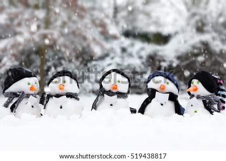 Five cute little snowman in a row, caught in a light snow shower. All wearing hats and scarfs with a carrot for a nose. Winter trees in the background.