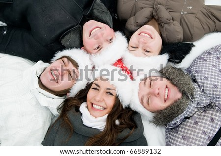 five jolly young boys and girls lying round on snow in winter wearing red hat