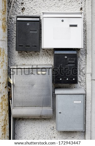 five old letterboxes at a wall