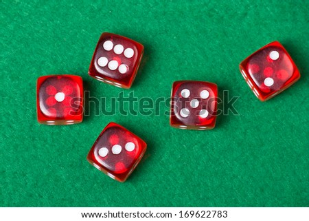 five red dices on green casino table