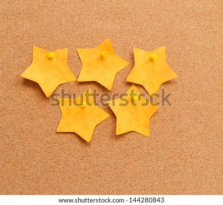 five stars sticky note on cork board