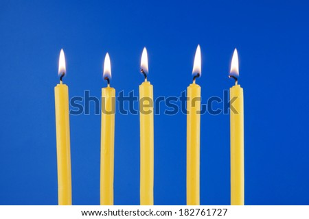 Five yellow burning candles on blue background