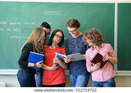 Five young people with glasses studying together