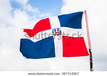 Flag of Dominican republic is waving on wind over blue cloudy sky background