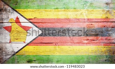 Flag of Zimbabwe painted on grungy wood plank background - stock photo