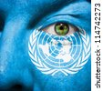 Flag painted on face with green eye to show United Nations support - stock photo