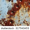 Flaking paint and bullet holes on rusty metal plate  - stock photo