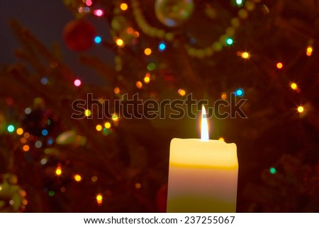 Flame of candle and Christmas tree ornaments