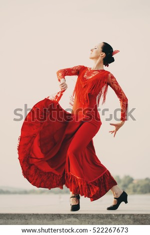 Flamenco dancer Spain womans in a long red dress dancing outside