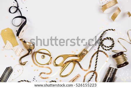 Flat Lay Christmas or Party Background with Colored Ribbons, Decorations, Confetti, and Wrapping Paper in Gold and Black. Room for Text in Middle.