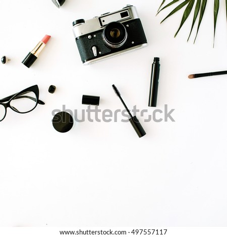 flat lay feminine arrangement with retro camera, accessories, glasses, cosmetics and palm branches on white, flat lay, top view