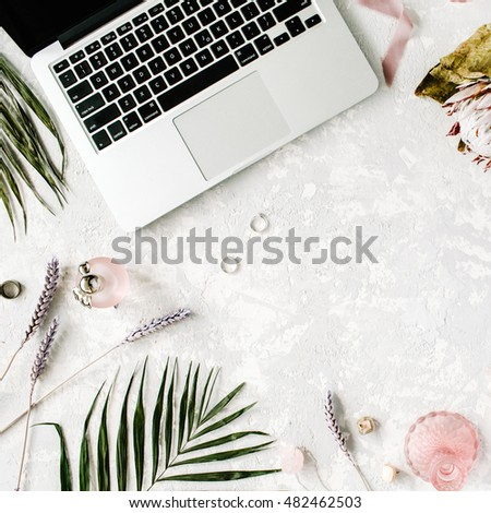 flat lay feminine home office workspace with laptop proteus flower necklace palm branches accessories k