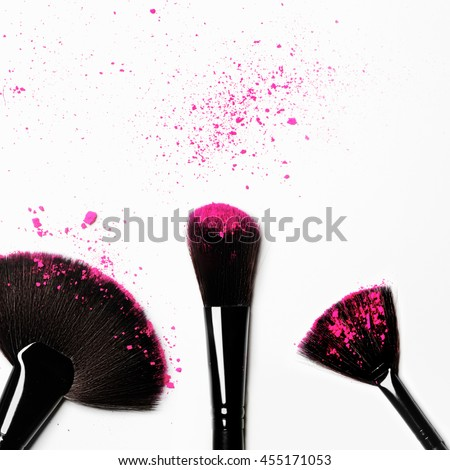 Flat lay. Makeup brush on white background with colorful pigment powder. Colorful eyeshadow