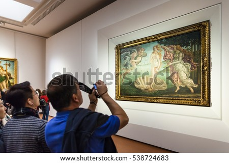 FLORENCE, ITALY - NOVEMBER 5, 2016: tourist takes photo in room of Uffizi Gallery. The Uffizi is one of the oldest museums in Europe, its origin refers to 1560, when Vasari designed large palace