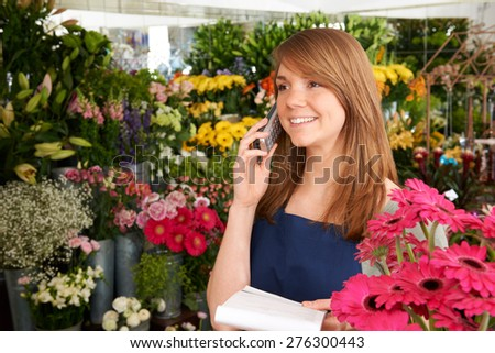 Florist In Shop Taking Order Over The Phone In Shop